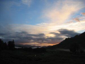 Sun setting over misty glen